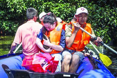 渍水导致行路难,郑志远(左)和叶黎鹏两个95后划着橡皮艇,每人差不多送出二十多名居民